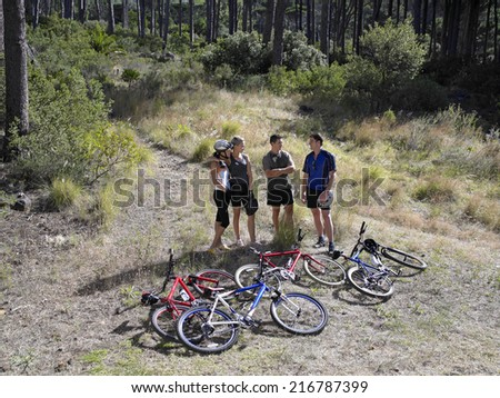 High angle view of two young couples standing near mountain bikes - stock photo