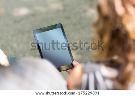 High angle view of university students holding digital tablet at campus - stock photo