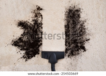 High Angle View Of Vacuum Cleaner Cleaning Dirt On Carpet - stock photo