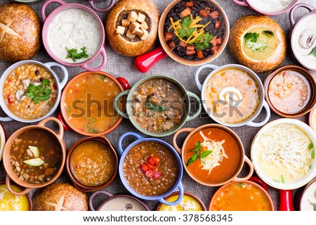 High Angle View of Various Comforting and Savory Gourmet Soups Served in Bread Bowls and Handled Dishes and Topped with Variety of Garnishes on Table Surface with Gray Tablecloth - stock photo