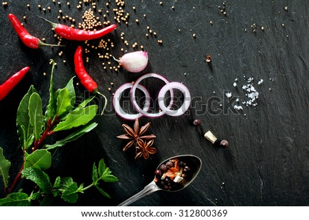 High Angle View of Various Fresh Herbs and Spices, Onion Slices, and Hot Peppers Scattered on Dark Gray Stone Surface with Copy Space - stock photo