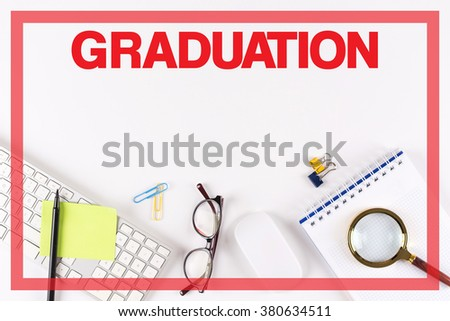 High Angle View of Various Office Supplies on Desk with a word GRADUATION - stock photo