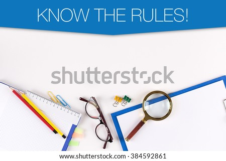 High Angle View of Various Office Supplies on Desk with a word KNOW THE RULES! - stock photo