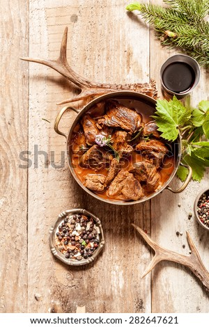 High Angle View of Venison Goulash Stew in Pot with Seasoning on Wooden Surface Surrounded by Deer Antlers and Tree Sprigs - stock photo