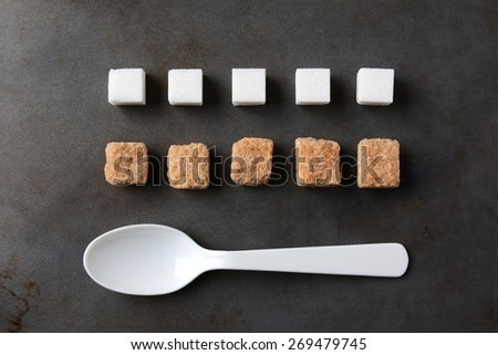 High angle view of white and brown sugar cubes and a white plastic spoon on a metal baking sheet. Five cubes of both the white and brown lumps line up in rows. Horizontal format. - stock photo