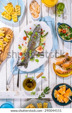 High Angle View of Whole Grilled Fish on White Platter with Garnish and Seasonings on Rustic White Wooden Table Surface with Other Seafood Dishes - stock photo