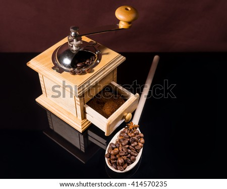 High Angle View of Wooden Spoon with Roasted Coffee Beans with Traditional Hand Grinder and Fresh Ground Coffee on Black Counter Surface with Copy Space - stock photo