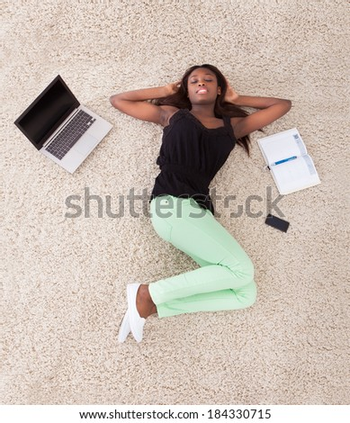 High angle view of young African American woman relaxing on rug at home - stock photo