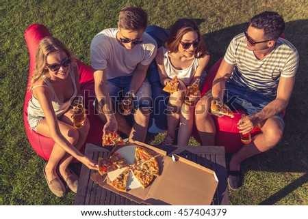 High angle view of young beautiful people in casual clothes and sun glasses eating pizza, talking and smiling, sitting on bean bag chairs while resting outdoors - stock photo