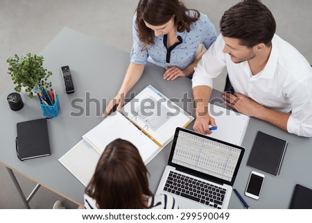 High Angle View of Young Business People Having a Meeting at the Table with Documents and Laptop Inside the Boardroom. - stock photo