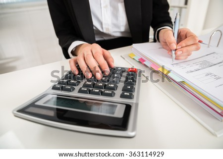 High angle view of young businesswoman doing financial calculation at desk in office - stock photo