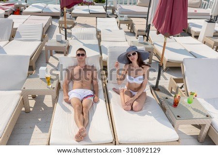 High Angle View of Young Couple with Tropical Drinks Relaxing on Lounge Chairs on Sunny Deck of Oceanfront Luxury Beach Resort - stock photo