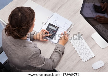 High Angle View Of Young Female Accountant Calculating Bills