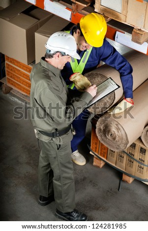 High angle view of young foreman with supervisor writing notes at warehouse