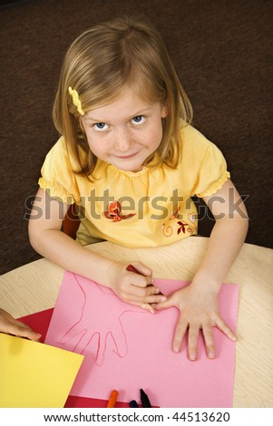 High angle view of young girl drawing. Vertically framed shot. - stock photo