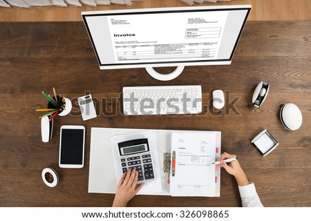 High Angle View Of Young Male Accountant Checking Invoice In Office - stock photo