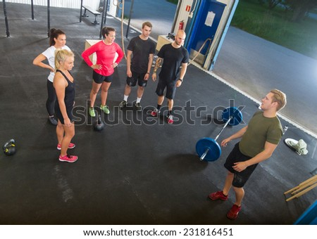 High angle view of young male trainer talking to athletes in gym - stock photo