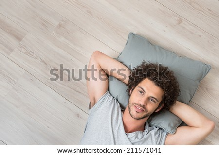 High Angle View Of Young Man Lying On Floor Thinking - stock photo