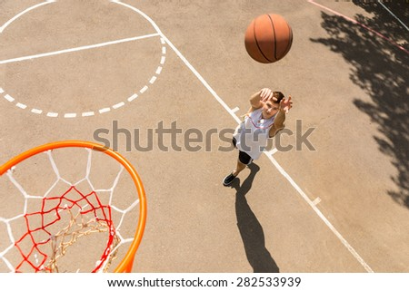 High Angle View of Young Man Playing Basketball, View from Above Hoop of Man Shooting Basketball - stock photo