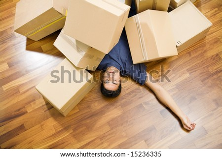 High angle view of young man sleeping underneath moving boxes - stock photo