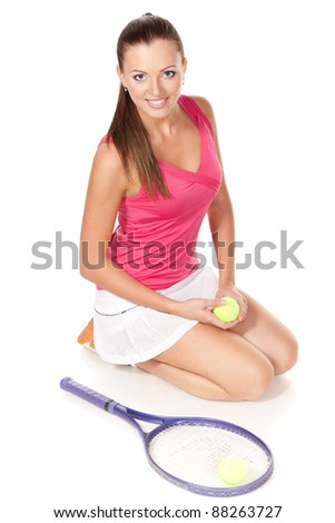 High angle view of young tennis female sitting on the floor with tennis ball in her hands, looking up - stock photo