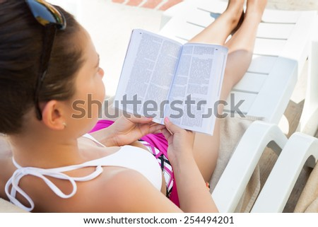 High angle view of young woman reading book on lounge chair at resort - stock photo