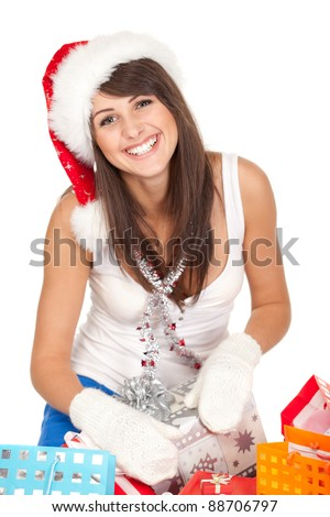 High angle view of young woman sitting with christmas presents wearing santa hat, shallow deep of field. - stock photo
