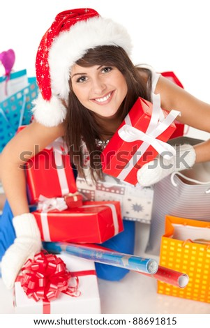 High angle view of young woman wrapping christmas presents wearing santa hat, shallow deep of field. - stock photo