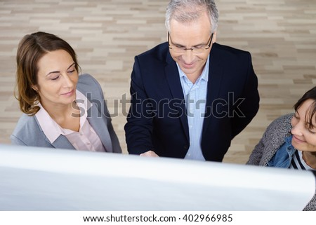 High angle view on cheerful trio of adult business people discussing something while standing in front of chart at office - stock photo