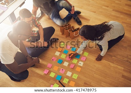 High angle view on female business owner writing on various sticky notes for workers on floor in small office with large bright window in background - stock photo