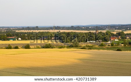 High angle view over fields to a large solar panel park providing renewable energy with a village in the background. - stock photo