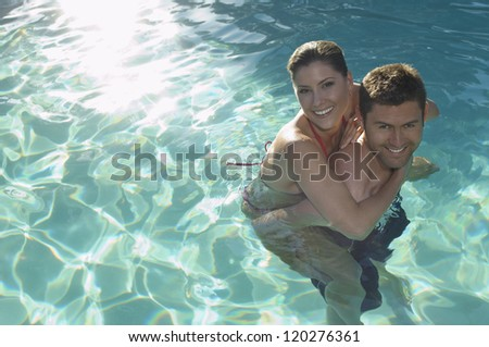 High angle view portrait of a couple having fun in swimming pool - stock photo