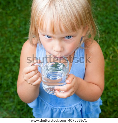 High angle view shot of blonde little girl wearing blue dress holding glass of water  in a summer garden focus on a glass