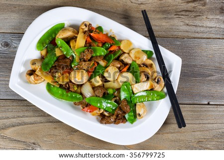 High angled view of Asian dish consisting of sliced juicy beef rice, onion, mushroom, green peas, and red pepper. Chopsticks on side of plate with rustic wood underneath.  - stock photo