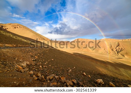 High Atlas mountain road with two rainbows, Morocco - stock photo