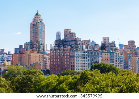 high buildings of midtown Manhattan viewed over the trees of Central Park - stock photo
