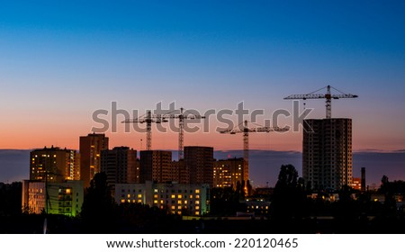 High buildings under construction with cranes and illumination at night - stock photo