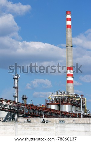 high chimney from oil refinery under sky