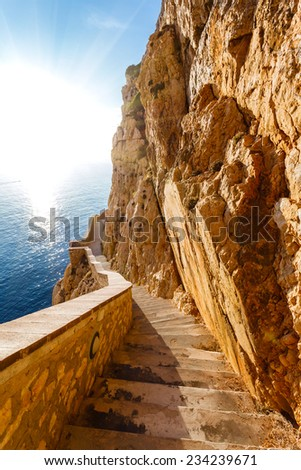 high cliffs and sea, staircase to Neptune Grotto in Sardinia, Italy - stock photo