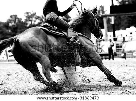 High contrast, black and white closeup of a rodeo Barrel Racer making a turn at one of the barrels (shallow focus on horse and exploding sand). - stock photo