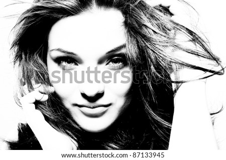 High contrast black and white portrait of beautiful girl with fluttering hair. - stock photo