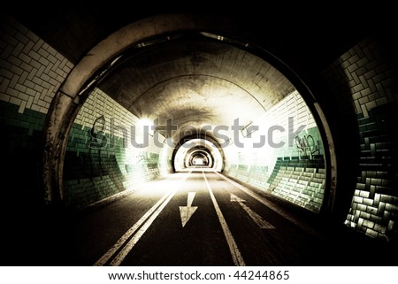 High-contrast exposure of a tunnel with arrows on the street - stock photo