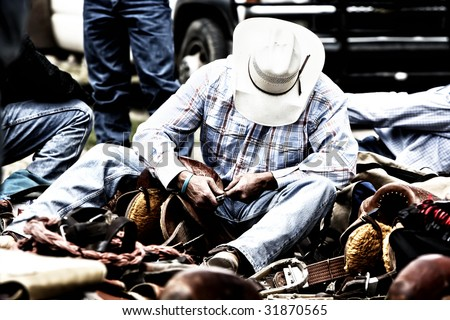 High contrast image of a rodeo cowboy behind the scenes working on his saddle. - stock photo