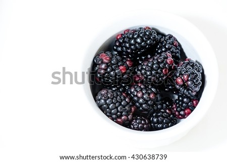 High contrast image of black berries in a white dish  on a white background.
