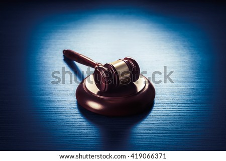 high contrast image of Judge gavel on a blue wooden background - stock photo