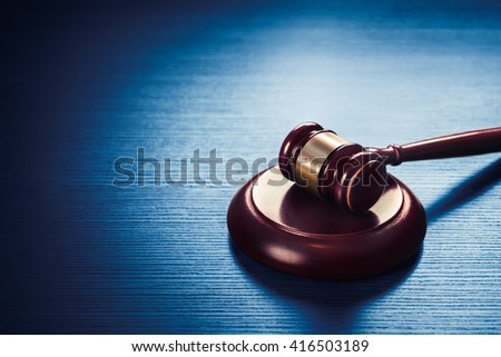 high contrast image of Judge's gavel on a blue wooden background - stock photo
