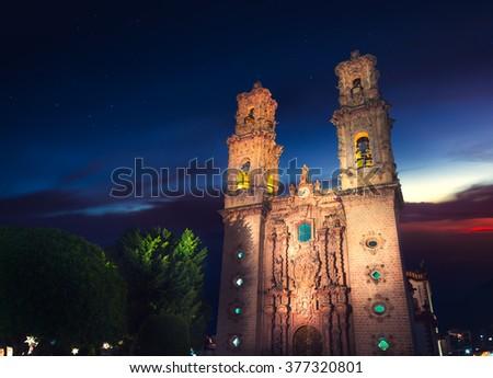 High contrast image of Santa Prisca de Taxco, Mexico at dusk. - stock photo