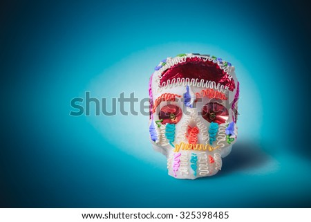 "High contrast image of sugar skull used for ""dia de los muertos"" celebration in a blue background - stock photo"