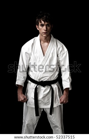 High Contrast karate male fighter on black background. - stock photo
