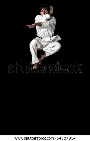 High Contrast karate young male fighter jumping on black background. - stock photo